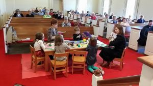 children at a table in the sanctuary during worship