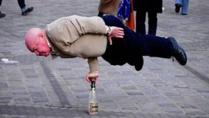 elderly man balancing on top of an empty bottle with his