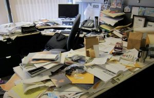 a desk cluttered with piles of paper