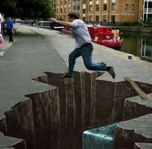 A man jumping over what appears to be a giant hole in the sidewalk. In reality, it's sidewalk chalk art, and there is no hole.
