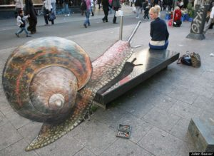 Sidewalk chalk art of what appears to be a giant snail crawling up a real sidewalk bench. A real woman has turned and appears to be looking at the snail.