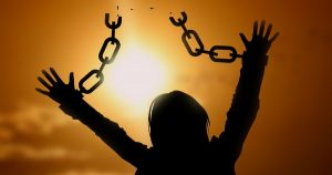 person standing with arms in the air with broken shackles on each wrist; a sunrise is in the background