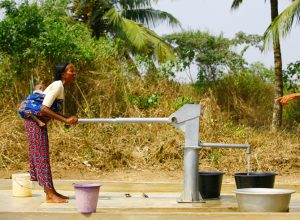 person standing at a water pump