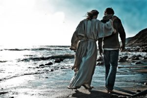 A modern man walking with Jesus along a beach