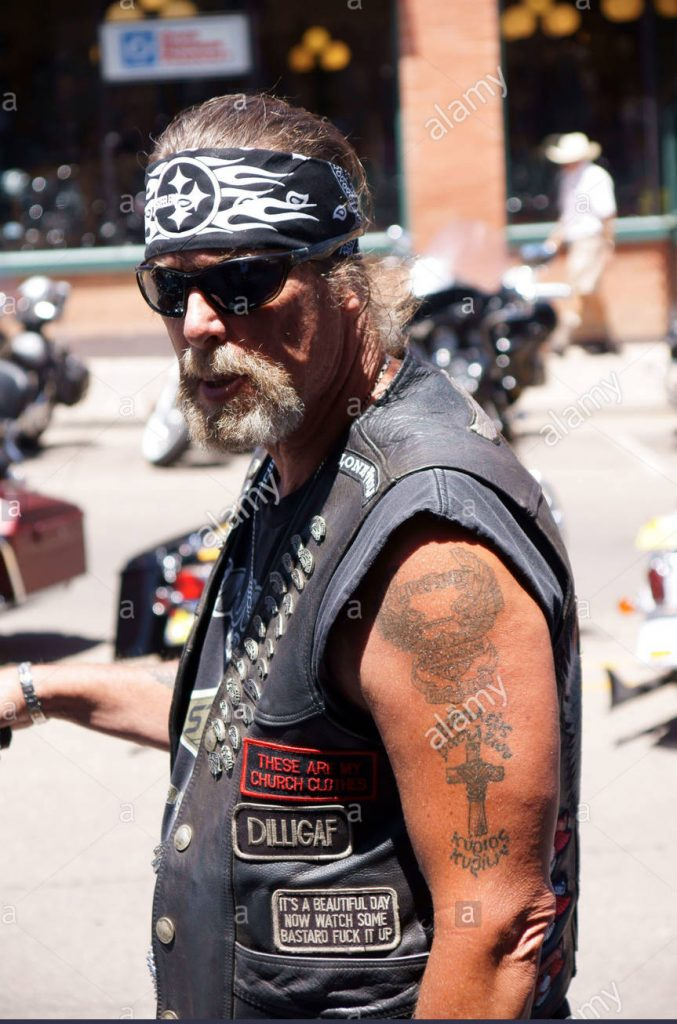 motorcycle rider with tattoos and wearing a sleeveless leather jacket and bandana on his head