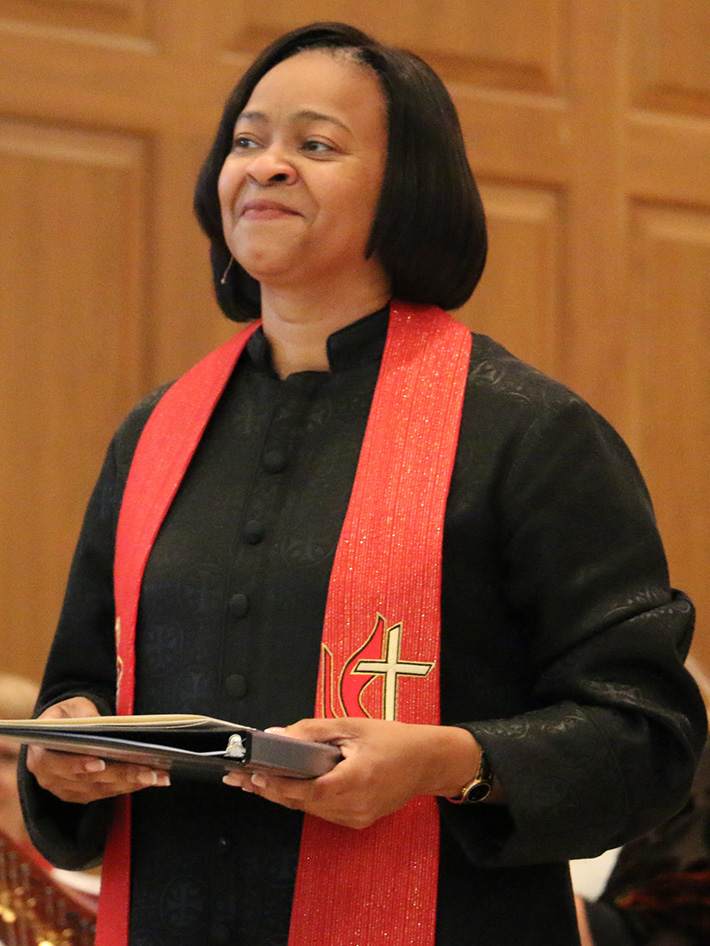 Bishop Sharma Lewis; African-American clergywoman wearing a black pulpit robe and a red stole