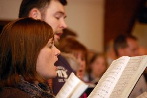 people singing from a hymnal during a worship service