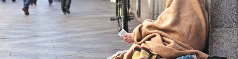 person covered by a blanket while sitting on the sidewalk leaning back against a building