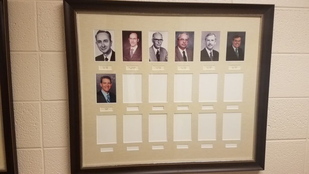 framed collection of photo of former pastors of Adrian First United Methodist Church; some spots are blank for future pastors.
