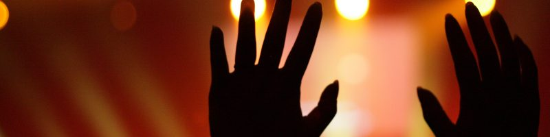 2 hands held up in worship against a red background