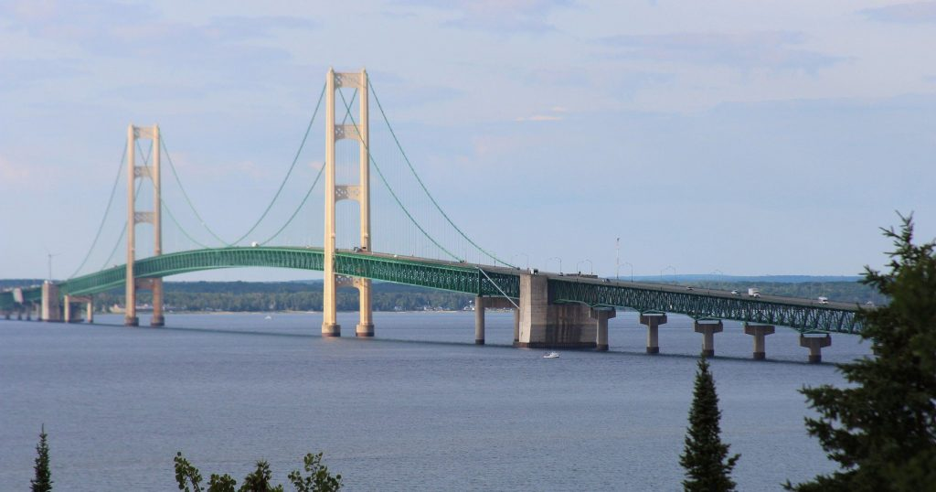 a 5-mile suspension bridge which connects Mackinaw City, Michigan and Saint Ignace, Michigan. The bridge is green and the towers are white.