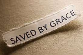 "slip of paper printed with the phrase, ""saved by grace."""