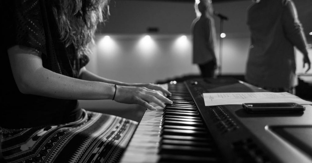 a woman playing a keyboard in worship
