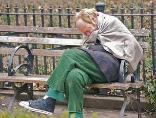 a homeless person sitting on a park bench