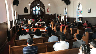 picture of a small congregation worshiping in a sanctuary.
